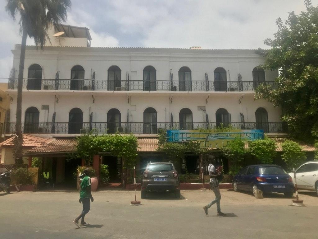 La facciata dell'Hotel de la Poste di Saint-Louis, con una macchina parcheggiata davanti e delle persone che camminano in strada
