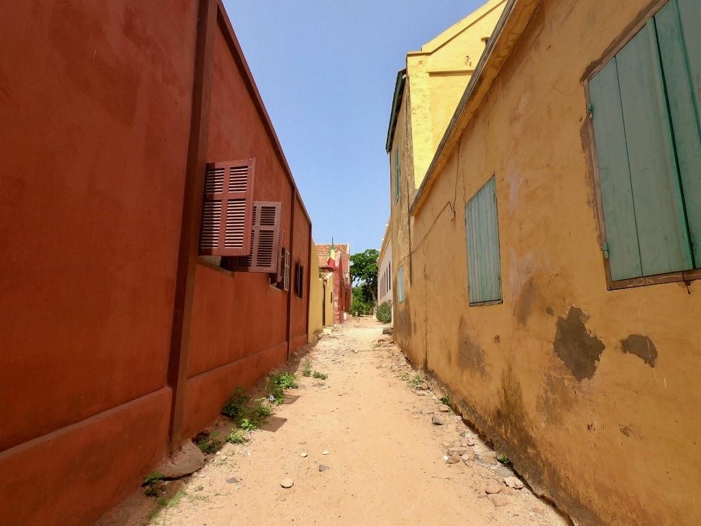 Una strada divide un edificio rosso e uno giallo a Gorée