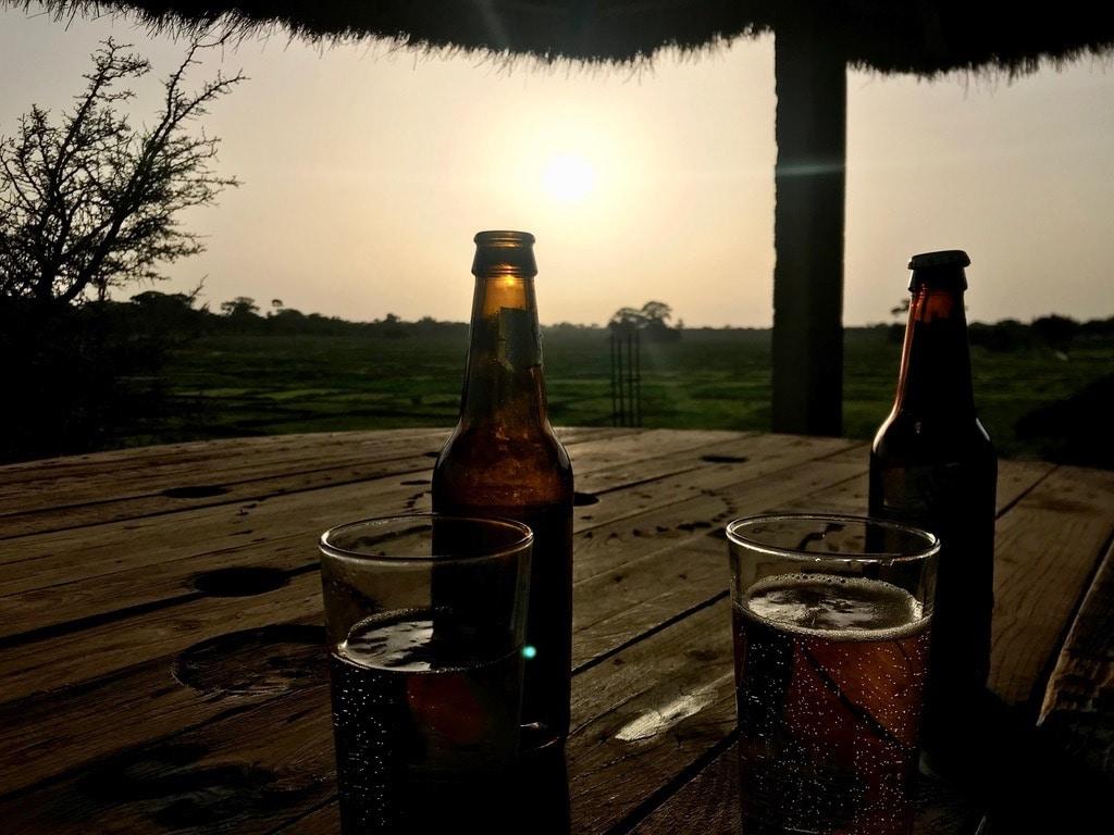 Due birre sul tavolino del Campement Alulum con il tramonto sullo sfondo