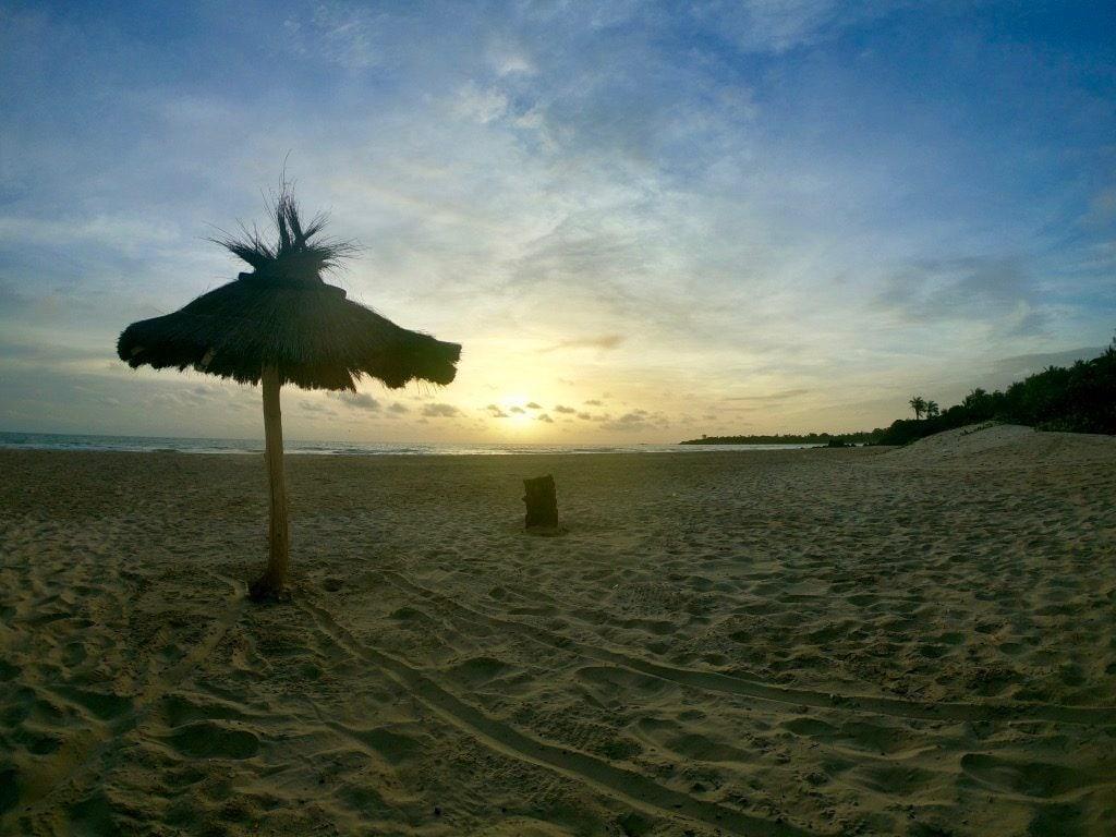 Un ombrellone sulla spiaggia di Cap Skirring al tramonto
