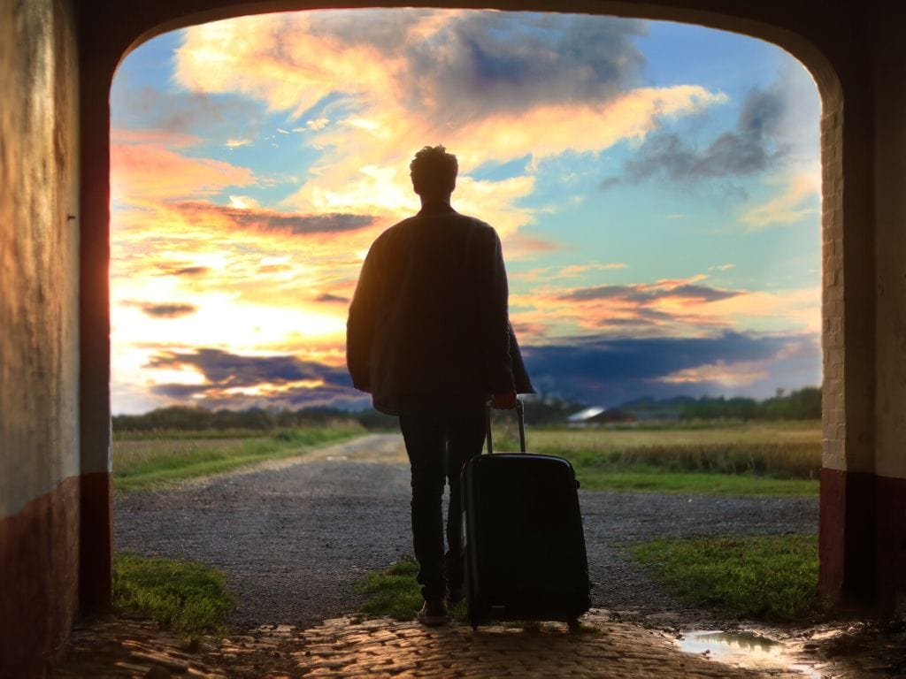 Persona al tramonto che trascina una valigia da aereo